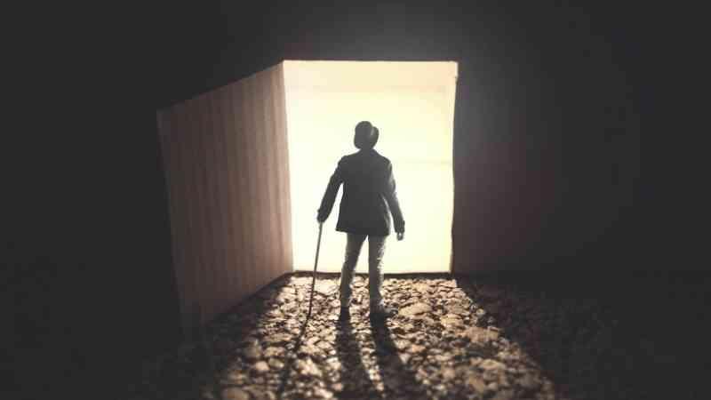 開いた扉の前に立つ、杖を持った男性