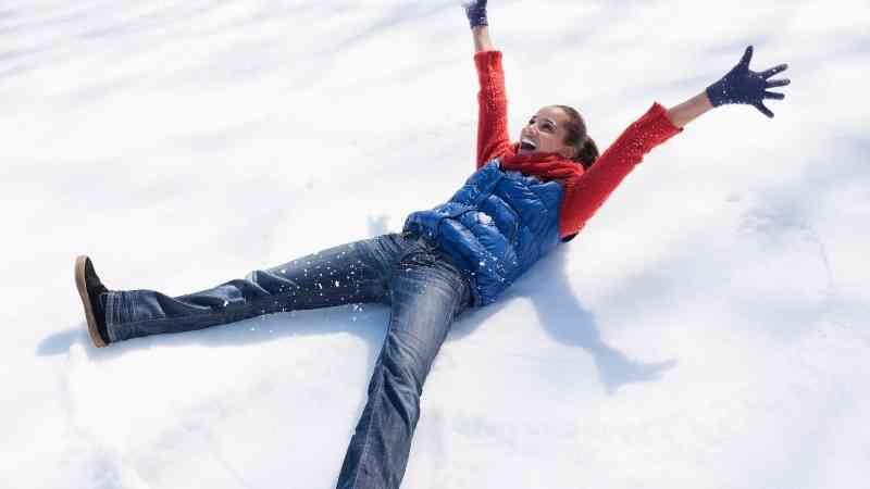 雪の上で楽しそうにはしゃぐ女性