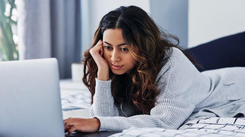 寝転んでパソコンを見る女性