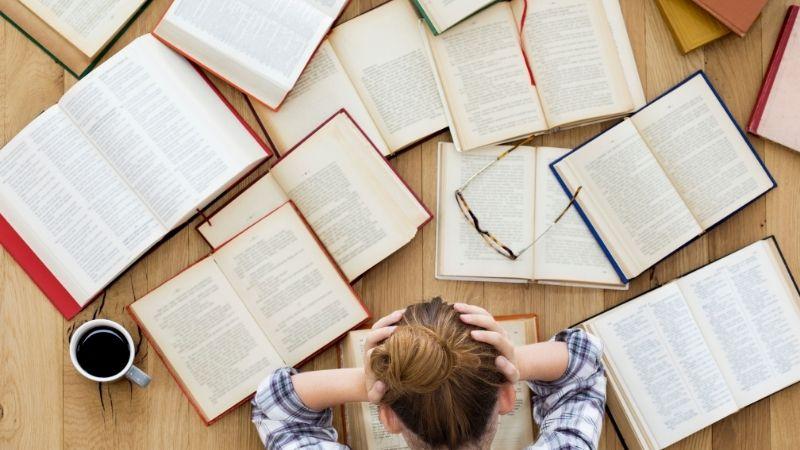 たくさんの本と頭を抱える女性