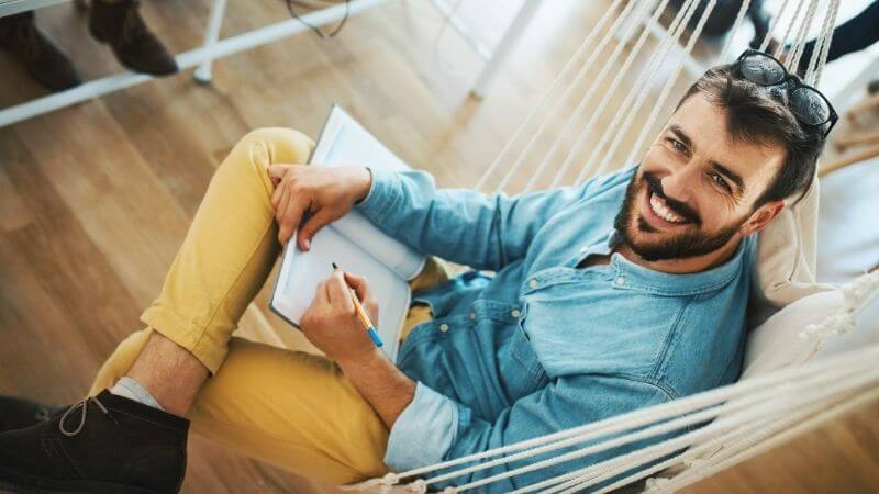 ノートに書き込む笑顔の男性