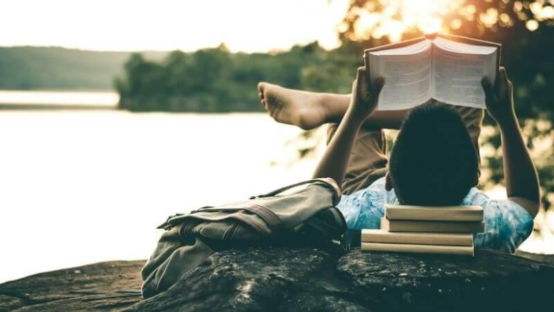 本を枕にして読書する男性