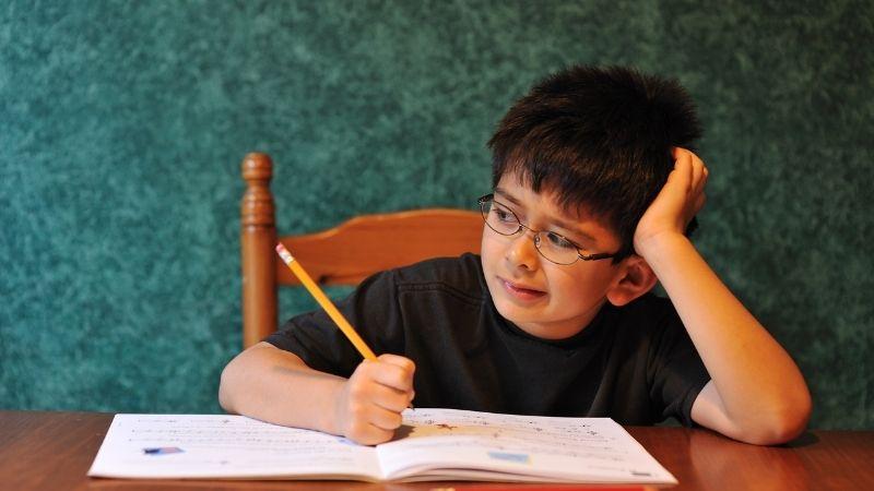嫌そうな顔で勉強する子供