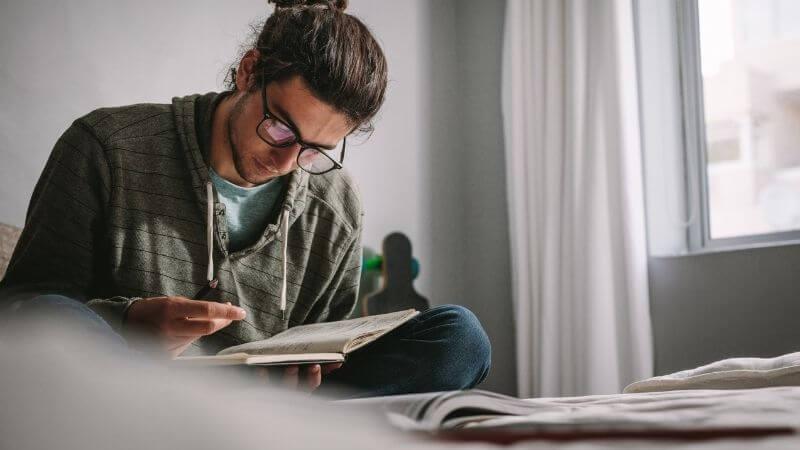 部屋で本で勉強する眼鏡の男性
