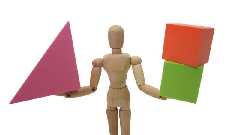 三角の積み木と資格の積み木を持った人形