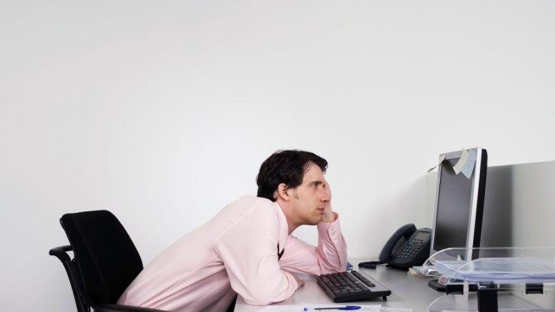 パソコンをつまらなそうに眺めるサラリーマン
